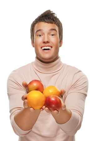 Portrait of smiling young man with oranges and apples, isolated on white background. photo