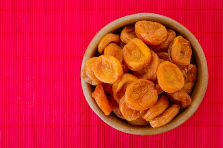 Wooden plate with dried apricots, on red bamboo tablecloth. Stock Photo - 18817612