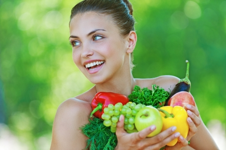 red head girl: Portrait of happy beautiful young woman with vegetables, against background of summer green park  Stock Photo
