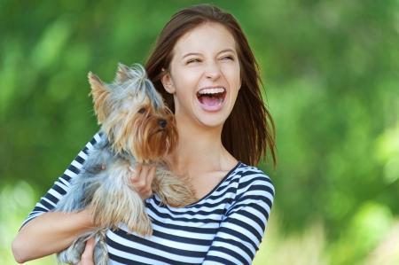mooie jonge vrouw gelukkig met lang donker haar in gestreepte trui die kleine hond