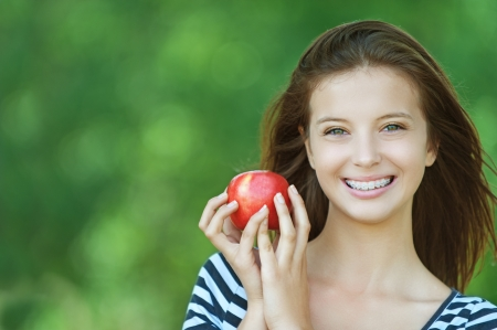 dark haired: Portrait of young cheerful attractive smiling woman eating red ripe apple at summer green park  Stock Photo