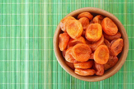 Wooden plate with dried apricots, on green bamboo tablecloth Stock Photo - 19140109
