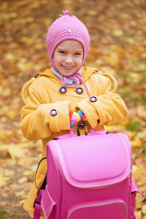 Beautiful smiling little girl in yellow coat with pink backpack goes to school. Stock Photo - 19379898