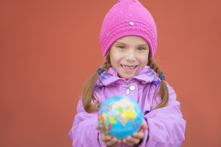 Little cheerful girl in pink jacket holding globe of Earth. photo