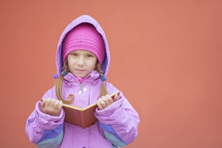 Beautiful little girl in pink coat reads orange book about stairs. Stock Photo - 19379889