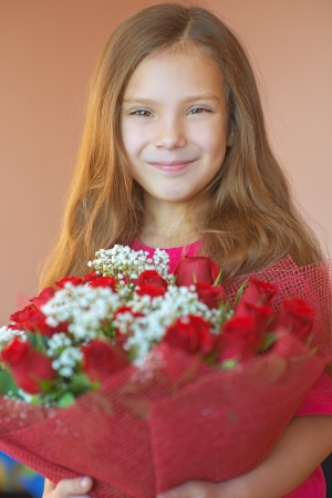 Beautiful smiling little girl with big bouquet of roses on birthday. photo