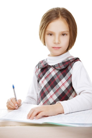 Little girl writing in notebook homework, isolated on white background. photo