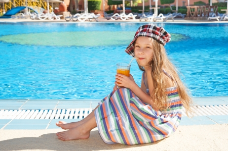 Little cheerful girl sitting near pool at resort and drinking juice. photo