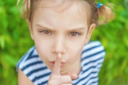 irritable: Little cheerful girl puts index finger to lips for silence, on green background. Stock Photo
