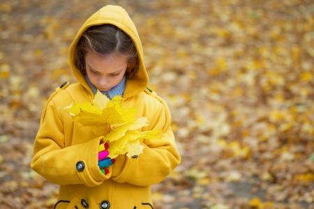Little sad girl in yellow coat holding autumn leaves. Stock Photo - 19536603