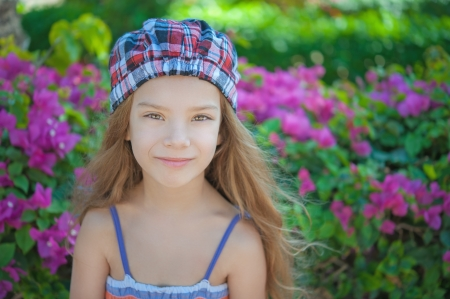 Portrait of beautiful smiling little girl in green summer city park. photo