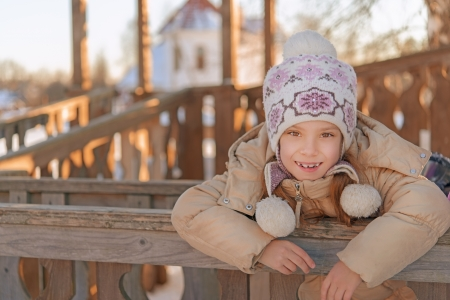 Portrait of beautiful smiling little girl in winter jacket on wooden children's playground. Stock Photo - 19536599