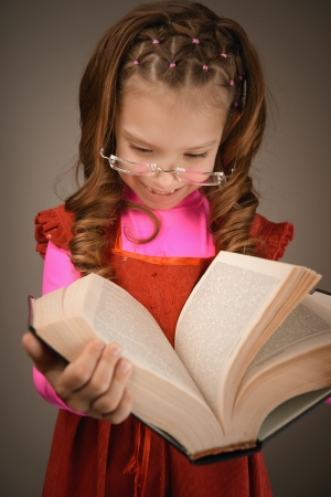 Portrait of beautiful smiling little girl in red dress and with book in studio Stock Photo - 19536612
