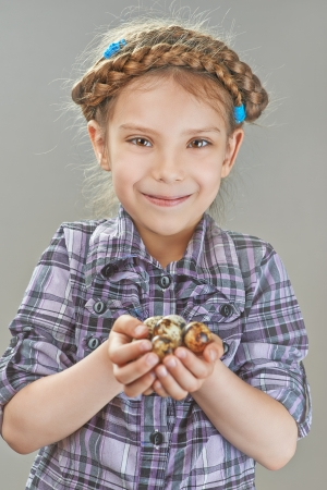 tresses: Portrait of beautiful little girl with quail eggs on gray background. Stock Photo