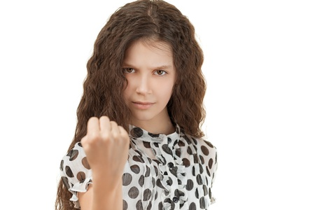 Beautiful sad schoolgirl threatening fist, isolated on white background. Stock Photo - 19536604