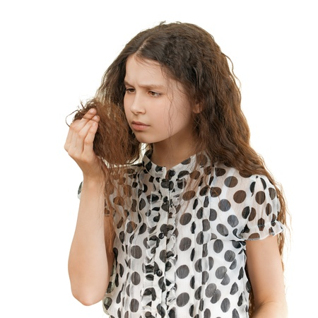 hair problem: Beautiful sad schoolgirl unhappy with her hair, isolated on white background. Stock Photo