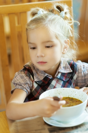 Girl-preschooler eats a tasty meal in cozy restaurant. photo