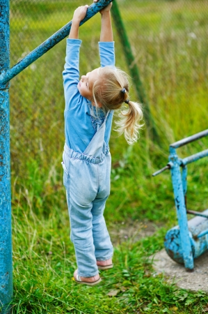 tresses: Beautiful little girl hanging on old exercise equipment in deserted park. Stock Photo