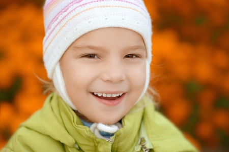 Beautiful smiling little girl in green jacket close-up. Stock Photo - 19536802