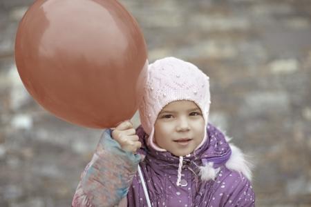 Ni�a hermosa en la chaqueta de color rosa con el globo rojo. Foto de archivo - 19536800