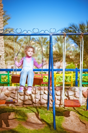 Portrait of beautiful little girl on swing in children's city park. photo