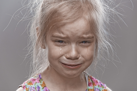 irritable: Beautiful sad little girl crying, on gray background.