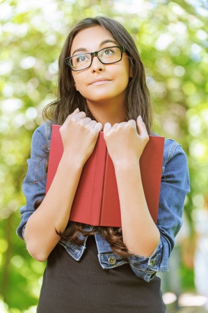 book jacket: Portrait of beautiful smiling dark-haired young woman with book in denim jacket, against summer green park. Stock Photo