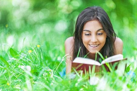 Beautiful smiling dark-haired young woman lying on grass and reading red book, against summer green park. photo