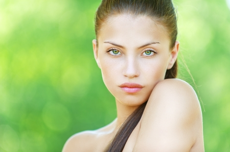 Portrait of young beautiful woman with bare shoulders, on green background summer nature. photo