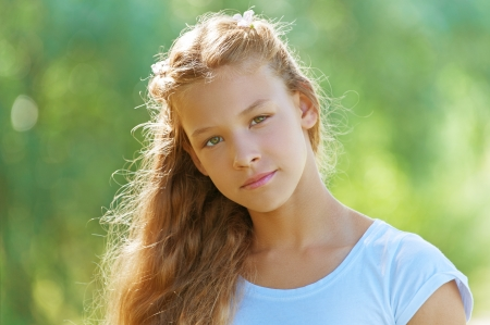 Portrait of beautiful smiling teenage girl in white blouse, against green of summer park. photo