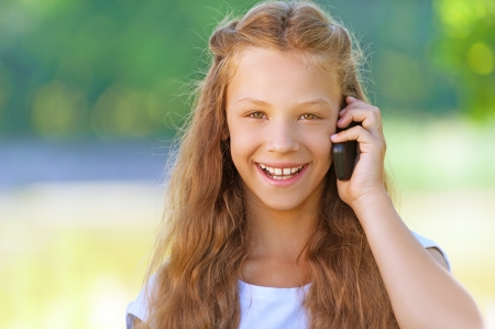 Beautiful laughing teenage girl talking on mobile phone, against green of summer park. photo