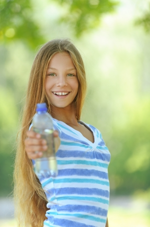Beautiful teenage girl in blue blouse with water bottle, against green of summer park. photo