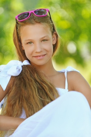 Portrait of smiling beautiful teenage in white dress and sunglasses, against green of summer park. photo