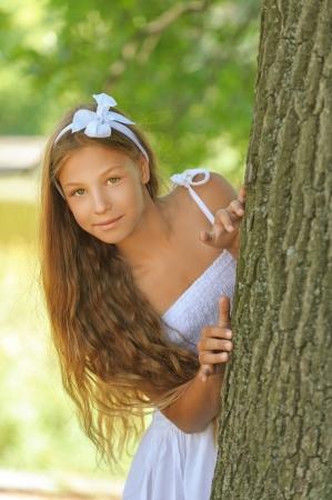 peeping: Beautiful frightened teenage peeping from behind tree, against green of summer park.