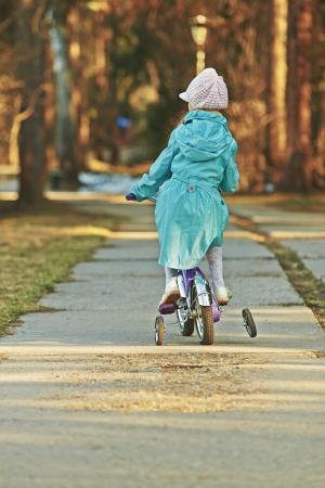 Girl in blue cloak rides bicycle in spring park, seen from behind. photo