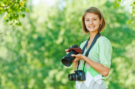 shootting: portrait of charming young beautiful short-haired woman in profile, photographs, against background of summer green nature