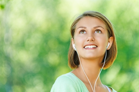portrait of young, pretty, quiet woman with short hair in headphones, smiling, against backdrop of summer Nature photo