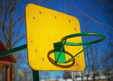 score board: Yellow basketball backboard with green ring without grid in courtyard apartment building.