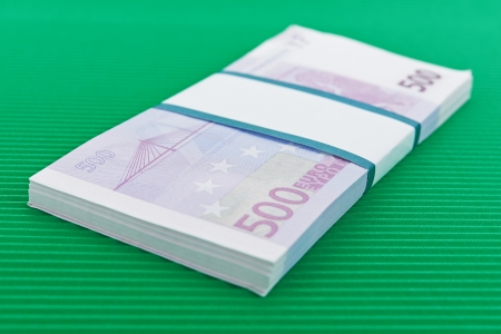Bundle of 500 Euro banknotes lying on green background. photo