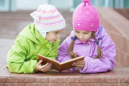 Two beautiful little girls in coats reads orange book. Stock Photo - 20384520