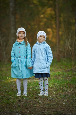 Two little girls in blue cloaks sister holding hands in autumn forest. photo