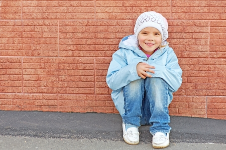 Beautiful little girl sitting on haunches beside brick wall. photo