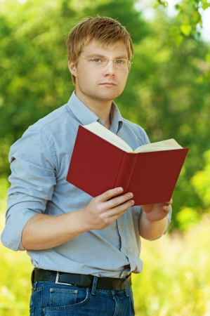 bible reading: young, charming, serious student (male) with glasses reading book on background of summer park