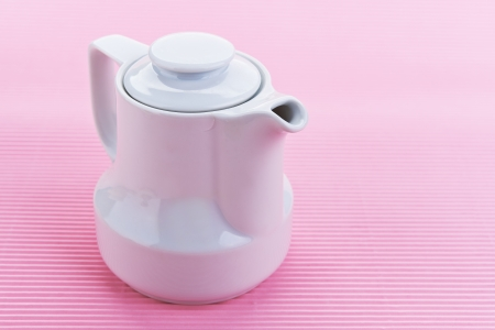 White porcelain milk jug on pink background. photo