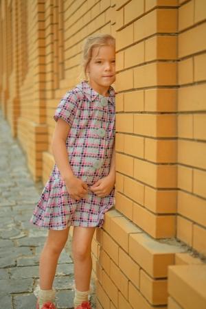 Little beautiful sad girl stands near yellow brick wall.