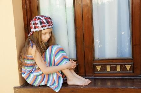 Little beautiful sad girl sitting near window. photo