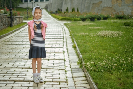 Beautiful little girl in jacket on sidewalk, against background of city street. photo