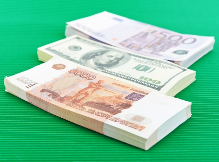 roubles: Banknotes - Russian rubles, euros and dollars on green background.
