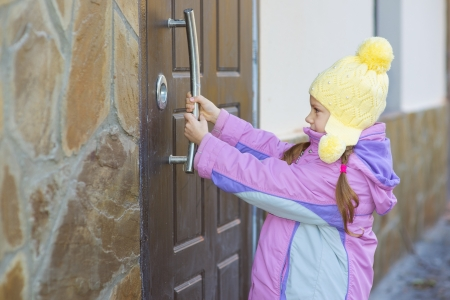 Beautiful little girl in pink jacket is trying to open big door. photo