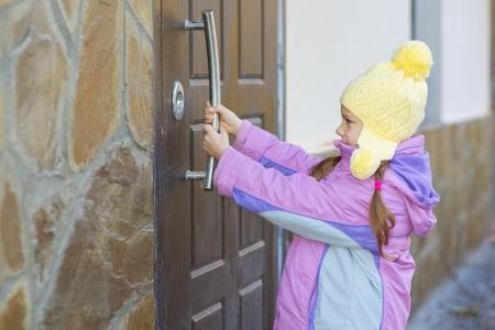 abriendo puerta: Niña hermosa en la chaqueta de color rosa está tratando de abrir la puerta grande. Foto de archivo